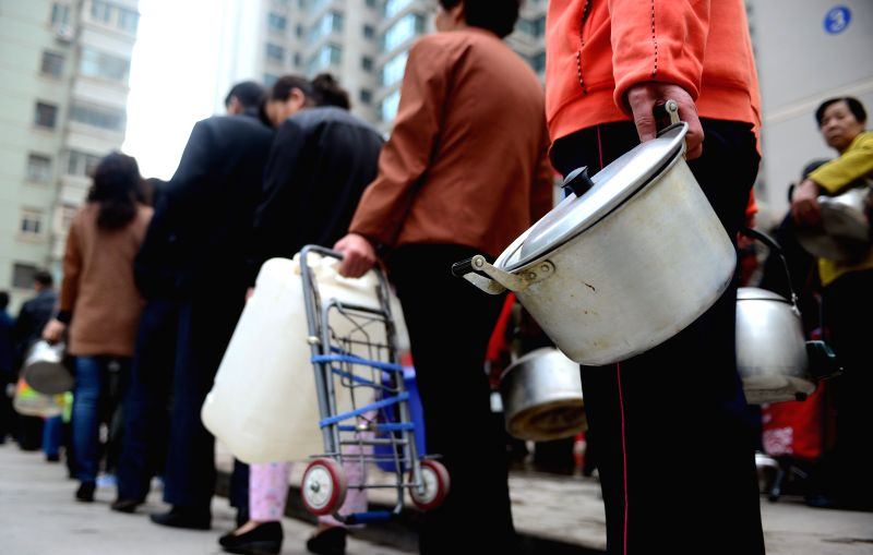 Residents queue up for water supplied by the local government in a community in Lanzhou, capital of northwest China's Gansu Province, April 12, 2014. Tap water in .