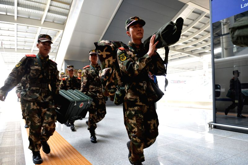Soldiers carry supplies and equipments to board a train at Lanzhou West Railway Station in Lanzhou, northwest China's Gansu Province, April 27, 2015. A team of 61 ...