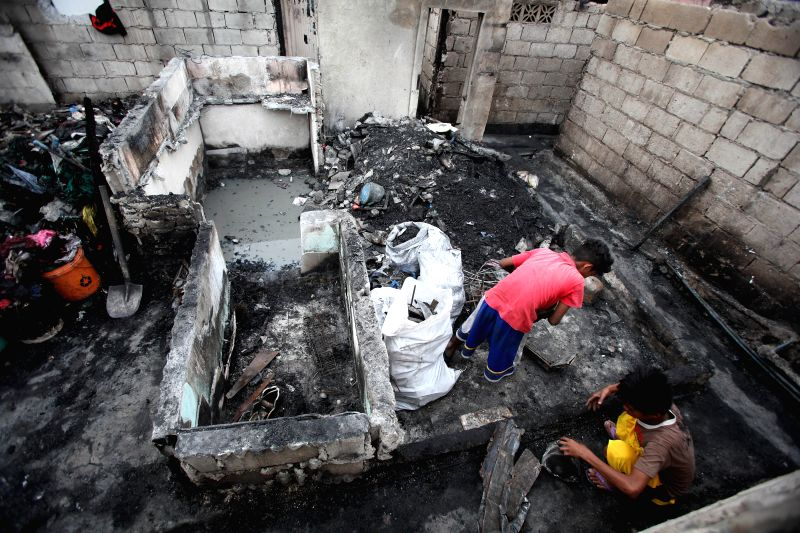 Residents look for reuseable materials from their charred houses after a fire at a slum area in Las Pinas City, the Philippines, Jan. 27, 2015. About 200 ...