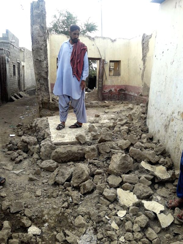 LASBELA, Jan. 31, 2018 - A man looks at the damaged wall of his house following an earthquake in southwest Pakistan's Lasbela on Jan. 31, 2018. At least one child was killed and nine others injured ...