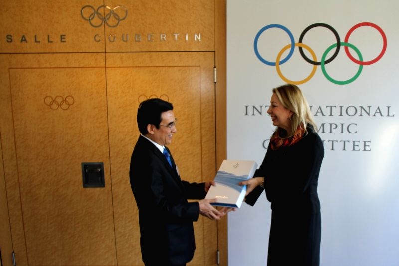 IOC head of Olympic bid city coordination Jacqueline Barrett (R) receives from the hands of Beijing 2022 Bid Committee president and mayor of Beijing Wang Anshun the