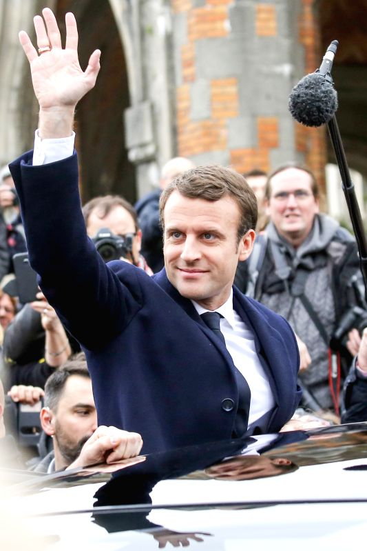 LE TOUQUET, April 23, 2017 - Emmanuel Macron (C), presidential candidate for the On the Move (En Marche) movement, leaves after he casted his ballots during the French presidential election in Le ...