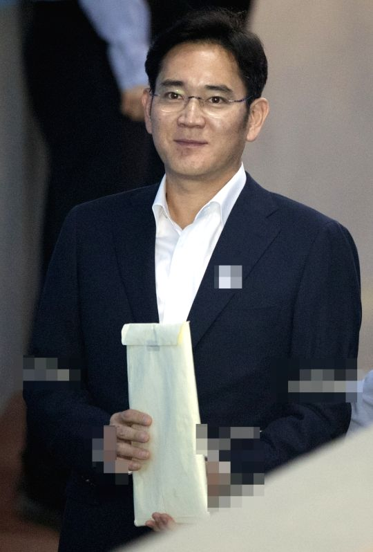 Lee Jae-yong, vice chairman of Samsung Electronics Co., enters the Seoul Central District Court in Seoul on May 17, 2017, to stand trial for alleged bribery related to the merger of two of Samsung's ...