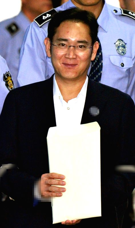 Lee Jae-yong, vice chairman of Samsung Electronics Co., smiles as he enters the Seoul Central District Court in Seoul on May 25, 2017, to stand trial for alleged bribery related to the merger of two ...