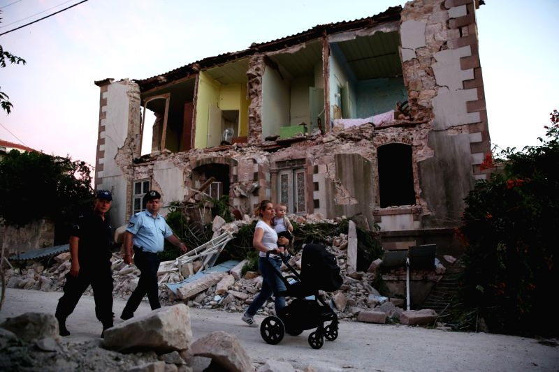 LESVOS ISLAND (GREECE), June 12, 2017 People walk past a destroyed house after an earthquake in Lesvos Island, Greece, on June 12, 2017. At least one person was killed and another 11 were ...
