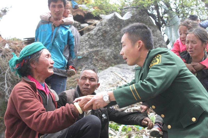 A soldier consoles an aged woman in Gyirong County in Shigatse (Xigaze), southwest China's Tibet Autonomous Region, due to an 8.1-magnitude earthquake in Nepal, ...