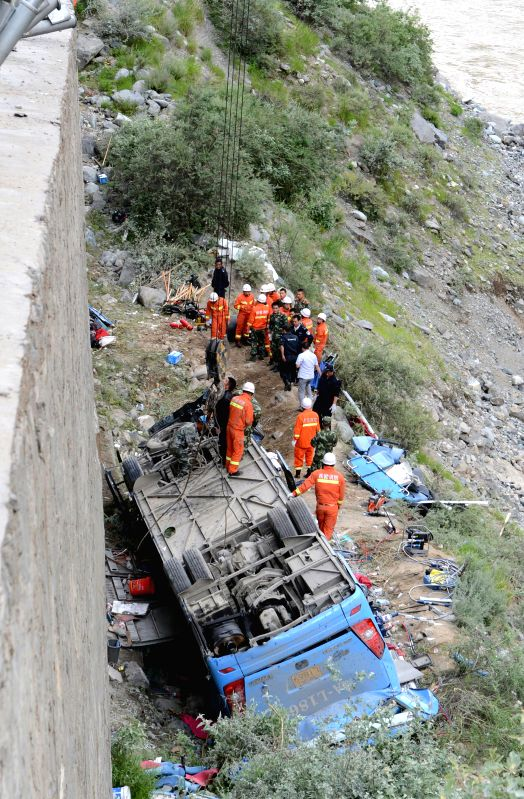 Rescuers work on the scene of a three-vehicle pile-up in Nyemo County, southwest China's Tibet Autonomous Region, Aug. 9, 2014. A tour bus carrying about 40 people ...