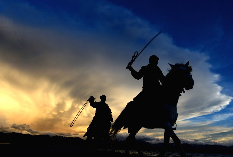 """Horse riders are seen by the Nam Co (""""heavenly lake"""" in Tibetan) in Damxung County, southwest China's Tibet Autonomous Region, June 23, 2014. The Nam Co has"""