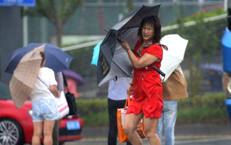 LIANYUNGANG, July 23, 2018 - Citizens walk against strong wind and rain on a street in Lianyungang City, east China's Jiangsu Province, July 23, 2018. Ampil, this year's 10th typhoon, brought heavy ...