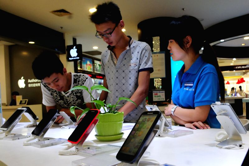 Sun Zhenkai (C), a soon-to-be freshman of Shandong Normal University, buys new smartphone in a store in Liaocheng, east China's Shandong Province, Aug. 19, 2014. .