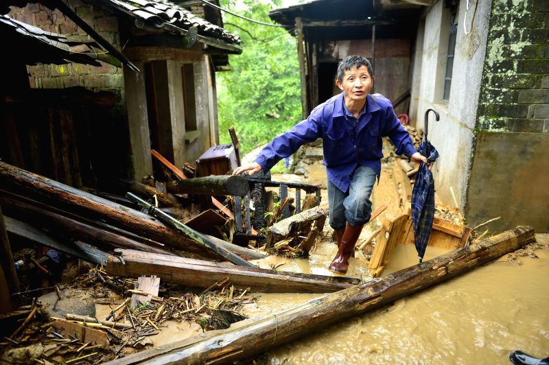 LICHUAN, May 9, 2016 - A man checks the condition of his house in Desheng Village of Lichuan County, east China's Jiangxi Province, May 9, 2016. A heavy rainstorm hit the county from May 7 to 8, ...