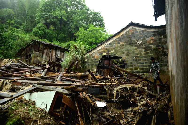LICHUAN, May 9, 2016 - A man checks the condition of destroyed houses in Desheng Village of Lichuan County, east China's Jiangxi Province, May 9, 2016. A heavy rainstorm hit the county from May 7 to ...
