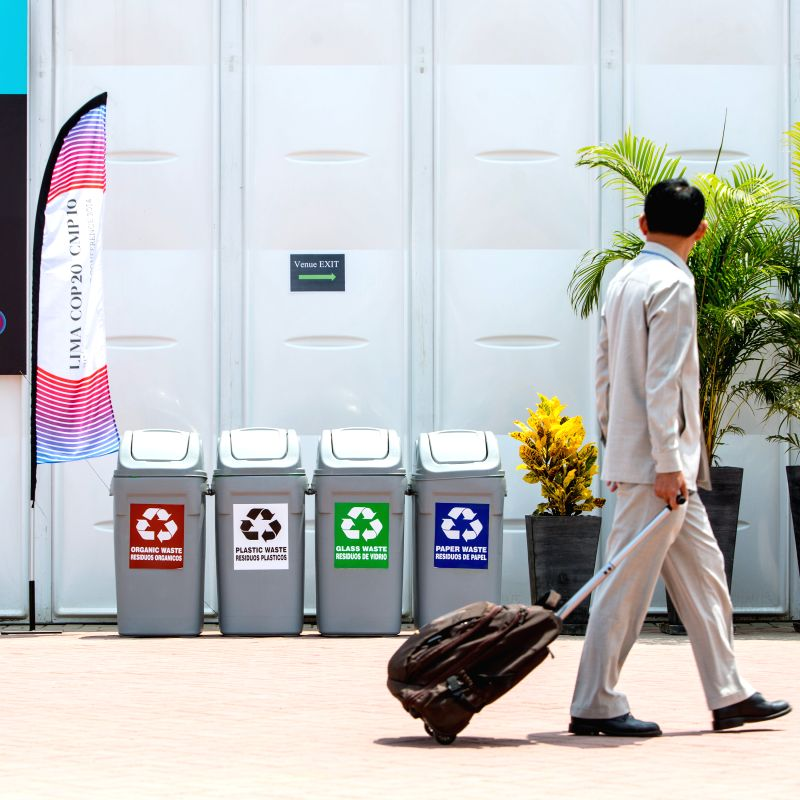 A man walks past the garbage classification bins in the Pentagonito COP 20 conference center in Lima, capital of Peru, Dec. 3, 2014.