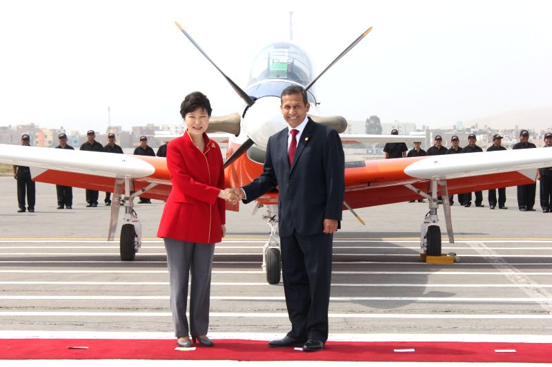 Peruvian President Ollanta Humala (R) shakes hands with his South Korean counterpart Park Geun-hye during the presentation ceremony of the first KT-1P aircraft, which ...