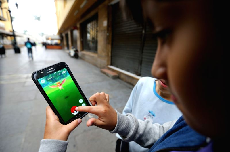 "LIMA, Aug. 8, 2016 - Children play ""Pokemon Go"" on a smartphone at Plaza Mayor in Lima, capital of Peru, on Aug. 7, 2016. ""Pokemon Go"" is a popular augmented reality game played ..."