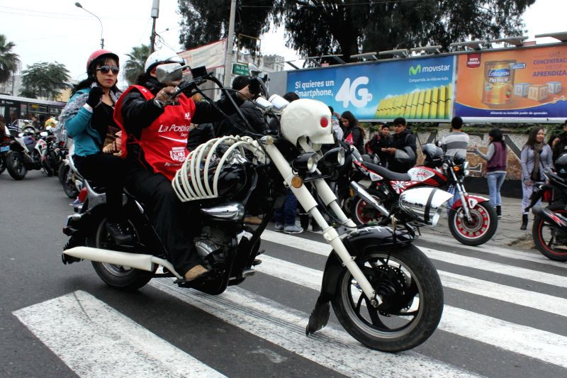 "A motorcyclist and a woman take part in the ""Patriotic Motorcycle Parade 2014"" in Lima city, capital of Peru, on July 20, 2014. Motorcyclists took part in ..."