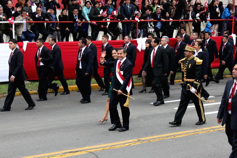 President of Peru Ollanta Humala (C, front) and First Lady Nadine Heredia (C, back) wave during the military parade as part of the celebration activities  of the ...