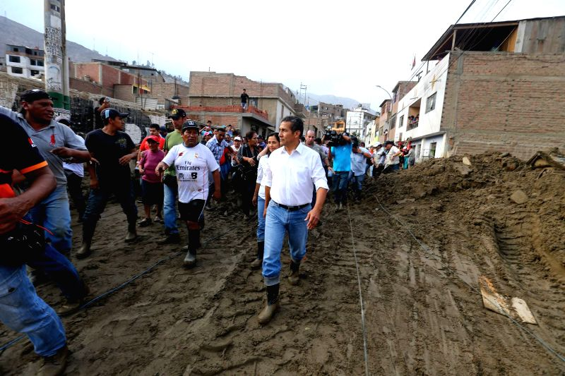 Peruvian President Ollanta Humala (C) makes a visit to a town affected by landslides in Santa Eulalia district, in Lima, Peru, on March 26, 2015. At least nine people ...