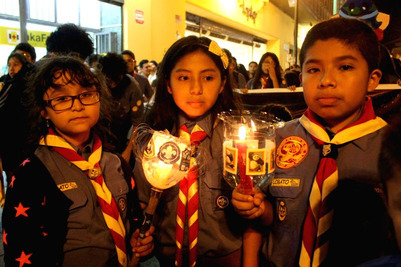 Children hold lighted candles during an event of the annual Earth Hour campaign, in the Main Square of Lima city, capital of Peru, on March 28, 2015. (Xinhua/Luis ...