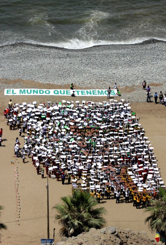 "Lima (Peru): Children form an image of a tree next to a sign reading ""The World We Want"" on the occasion of the UN Climate Change Conference COP 20, on a beach in Lima, Peru, on Dec. 4, ..."