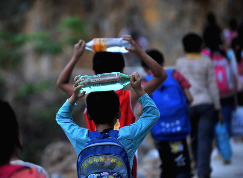 Children of Nongxin Elementary School take bottled drinkable water on the way to school in Haokun Village of Lingzhan Yao Autonomous Township in Lingyun County, ...
