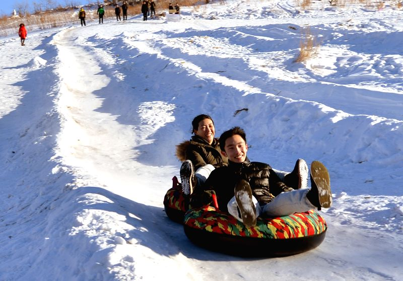 Photo taken on Feb. 2, 2015 shows visitors having fun in Songling Village, Linjiang City of northeast China's Jilin Province. As tourism on snow develops, scenic ...
