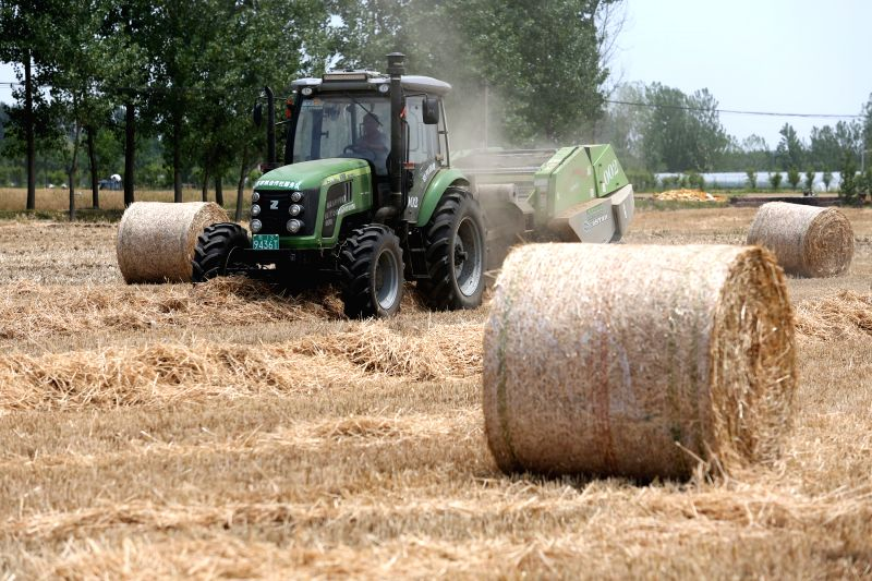LINYI, June 4, 2017 - An agricultural vehicle packs up collected wheat straw in the field in Dongqin Village of Tancheng County of Linyi City, east China's Shandong Province, June 4, 2017. The ...