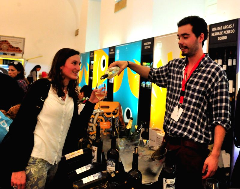 A visitor tastes Portuguese wine during the Lisbon Fish and Flavours Festival in Lisbon, Portugal, on April 12, 2014. The festival is held from April 3 to April 13.