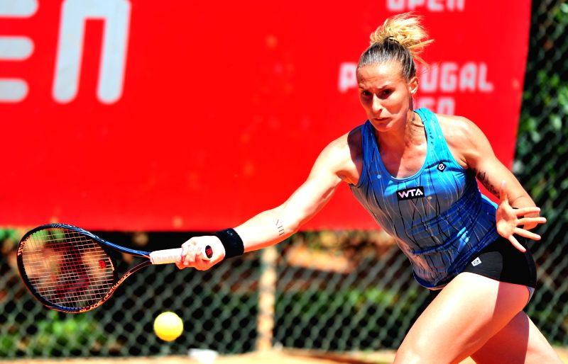 Polona Hercog of Slovenia hits a return to Stefanie Voegele of Switzerland during the women's sigles match at the 2014 Portugal Tennis Open in Lisbon, capital of ...