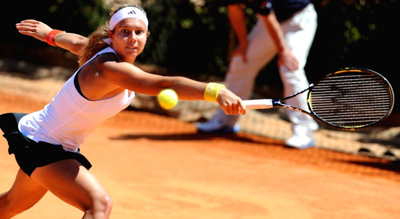 Stefanie Voegele of Switzerland hits a return to Polona Hercog of Slovenia during the women's sigles match at the 2014 Portugal Tennis Open in Lisbon, capital of ...
