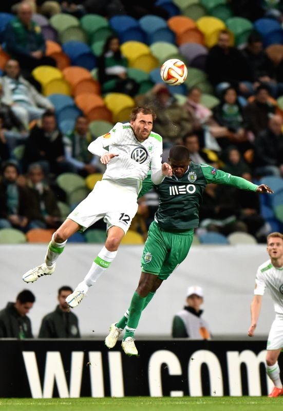 Sporting's William (R) vies for the ball with Wolfsburg's Bas Dost during the UEFA Europa League round of 32 second leg match between Sporting Clube de Portugal and ...