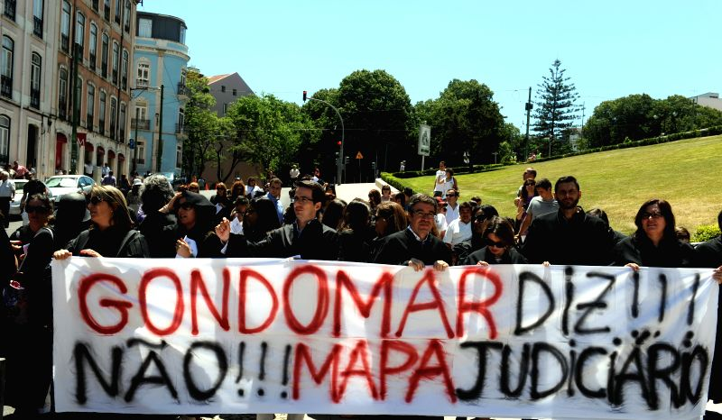 People take part in a demonstration against a new law, which will eliminate courts in the country in Lisbon, Portugal, on July 15, 2014. Hundreds of lawyers crowded .