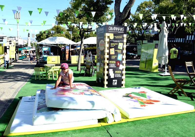 LISBON, June 11, 2017 - A child reads a giant book during the 87th Portugal's book fair in Lisbon, Portugal, June 7, 2017. The fair, which kicked off on June 1, will last until June 18 with an ...