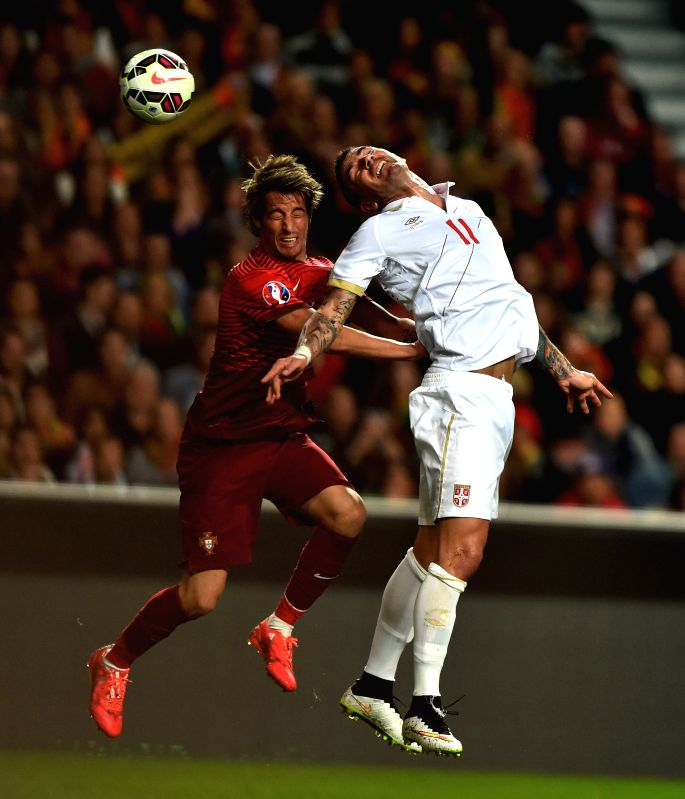 Fabio Coentrao (L) of Portugal heads the ball with Aleksandar Kolarov of Serbia during their UEFA Euro 2016 Group I qualifying match in Lisbon, Portugal, March 29, ...