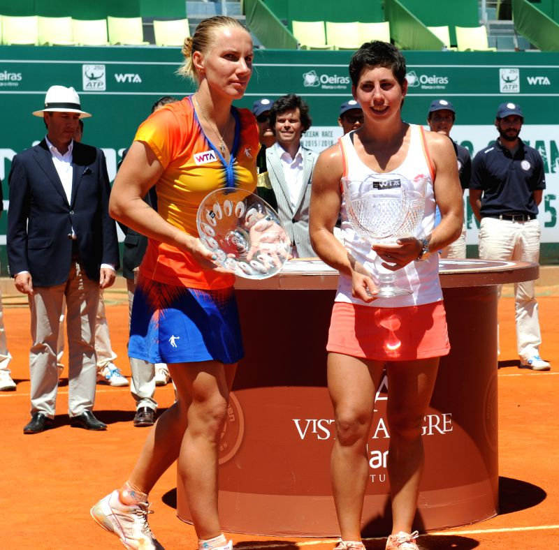 Carla Suarez Navarro (R) of Spain and Svetlana Kuznetsova of Russia react during the awarding ceremony after their women's singles final match at the 2014 Portugal ...