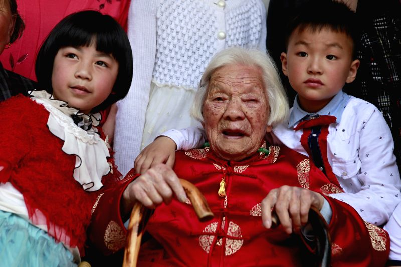 Zhu Jinjuan (C) poses for photos with two of her great-great-grandchildren at a family get-together celebrating her 110th birthday in Chiyang Village under Jinyun ...