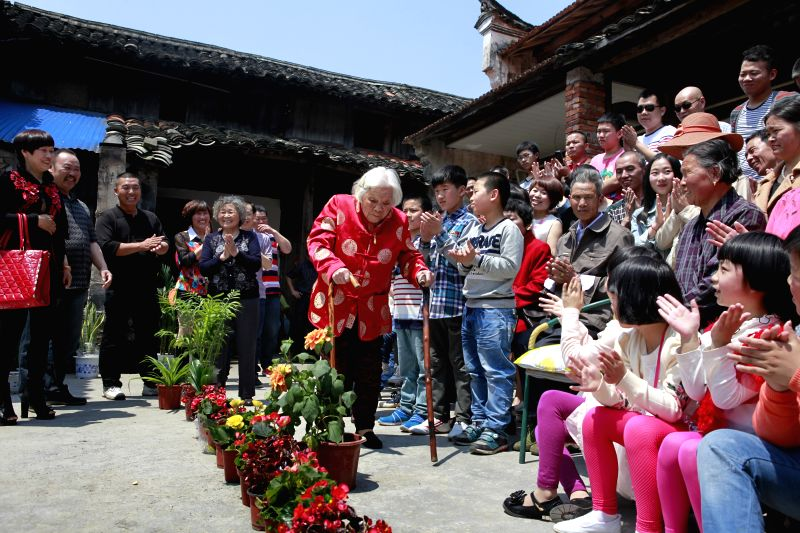 Zhu Jinjuan (C) prepares for a family photo at a get-together celebrating her 110th birthday in Chiyang Village under Jinyun County of Lishui, east China's Zhejiang ...