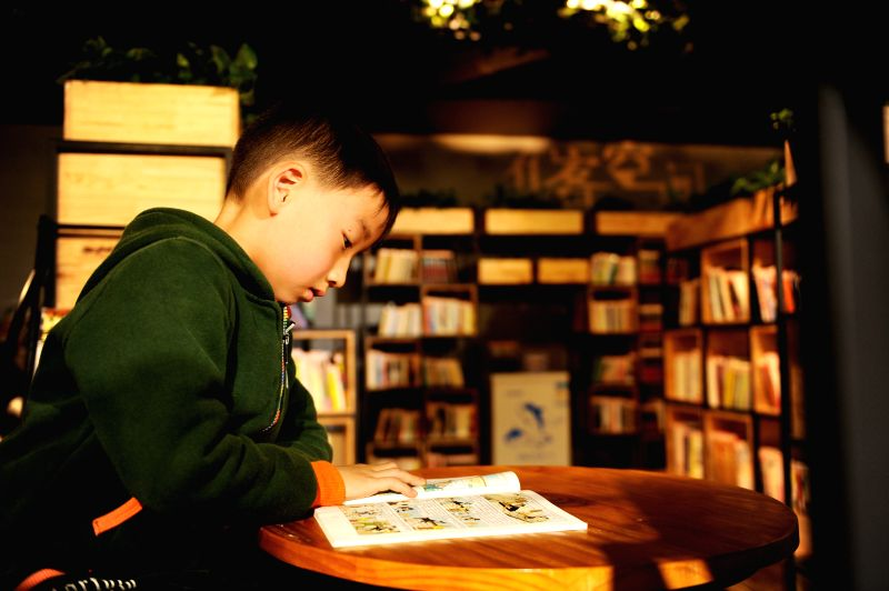 LIUPANSHUI, April 23, 2017 - A boy reads a book in a book bar in Liupanshui, southwest China's Guizhou Province, April 23, 2017. The World Book Day falls on Sunday.  (Xinhua/Tao Liang)