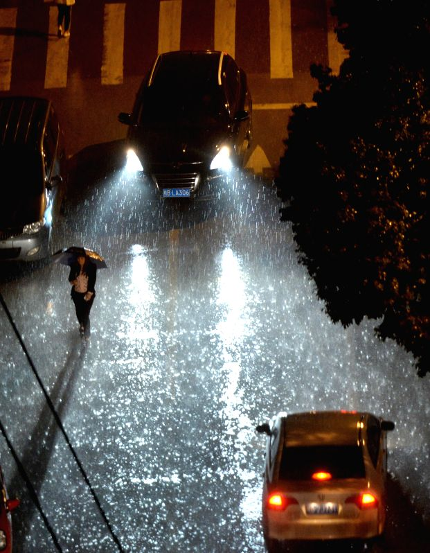 A pedestrian walks on a flooded road amid rainfall in Liuzhou City, south China's Guangxi Zhuang Autonomous Region, April 25, 2014. A rainstorm lashed the city at .