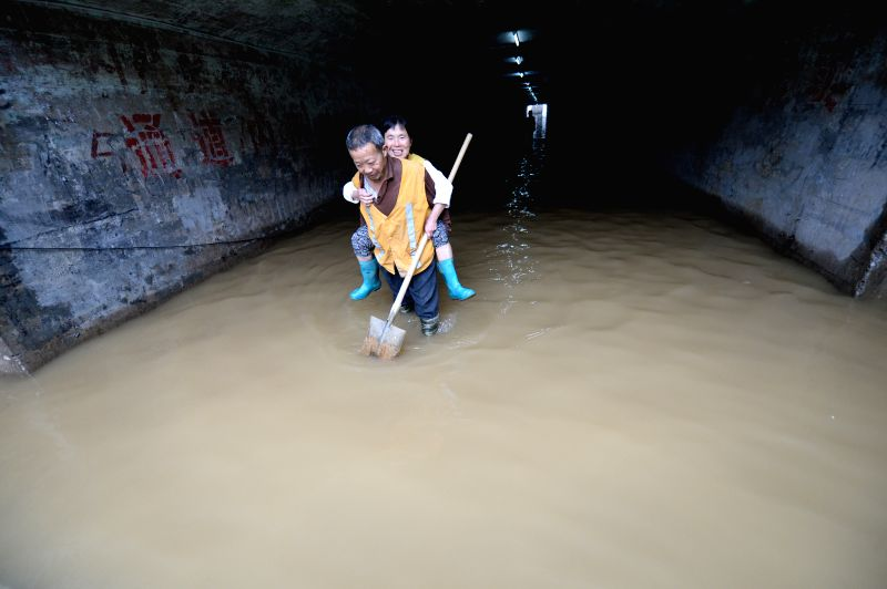 A sanitation worker carries a woman on the back as they walk through a railway culvert in Liuzhou City, south China's Guangxi Zhuang Autonomous Region, April 26, ..