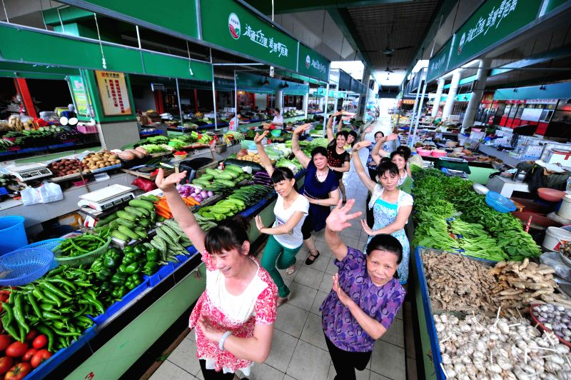 Female dealers dance in the passage of Sulu Agricultural Market in Nanning, capital of Guangxi Zhuang Autonomous Region, July 13, 2014. Female dealers here took ...