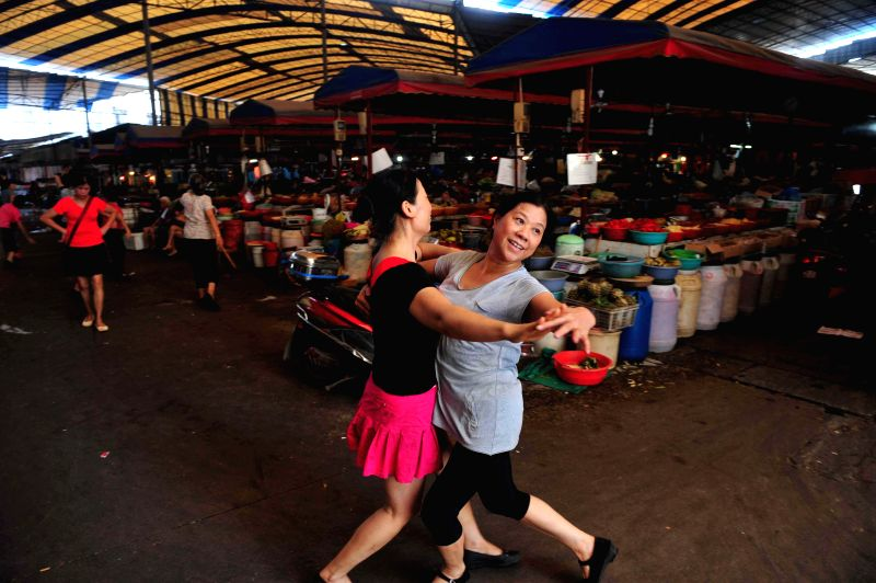 Female dealers dance in the passage of Qianjin Market in Liuzhou, south China's Guangxi Zhuang Autonomous Region, July 28, 2014. Female dealers here took advantage .