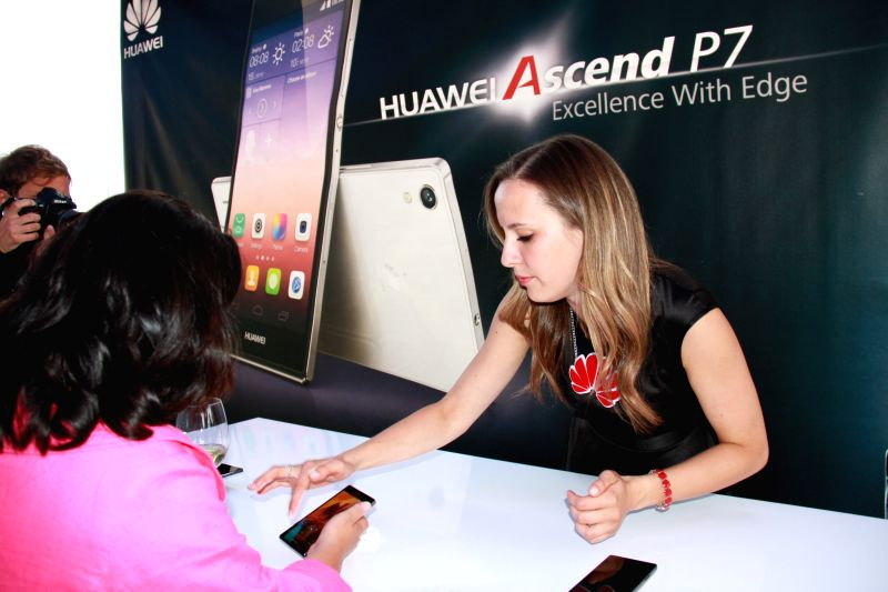 A staff member shows an Acsend P7 smart phone to a guest during a presentation by Huawei Technologies Co. Ltd, a Chinese telecommunication giant, to introduce its
