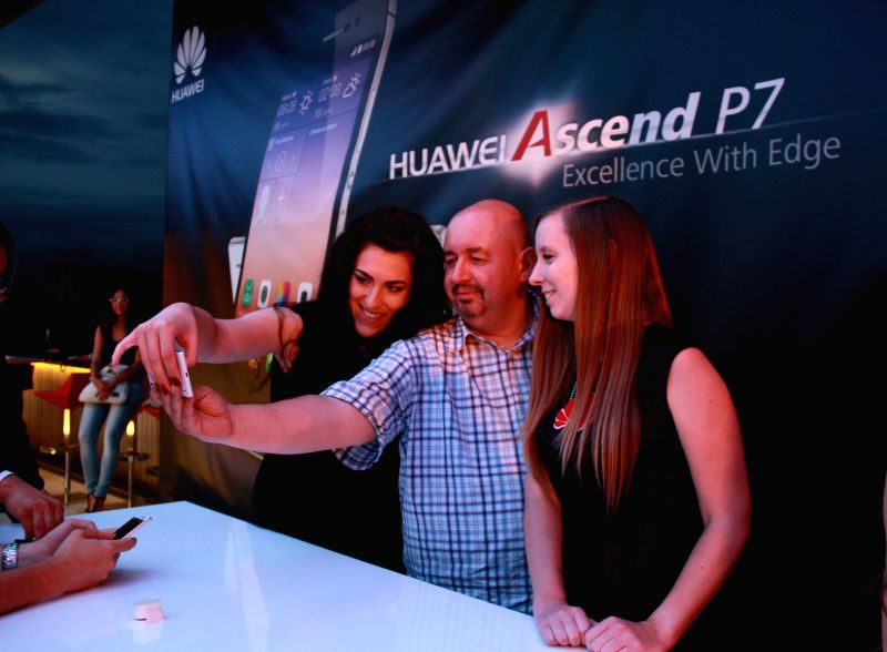 People take a selfie using an Acsend P7 smart phone during a presentation by Huawei Technologies Co. Ltd, a Chinese telecommunication giant, to introduce its ...