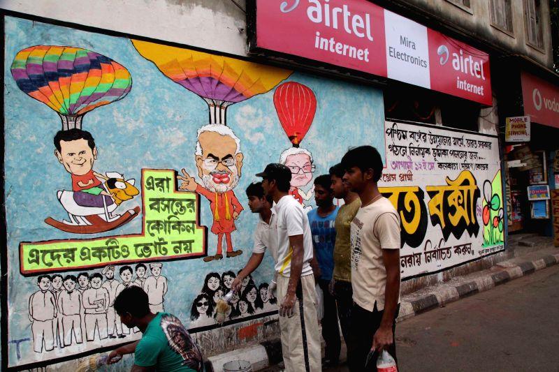 Local artists make a political graffiti on a wall ahead of Lok Sabha election in Kolkata on April 18, 2014.