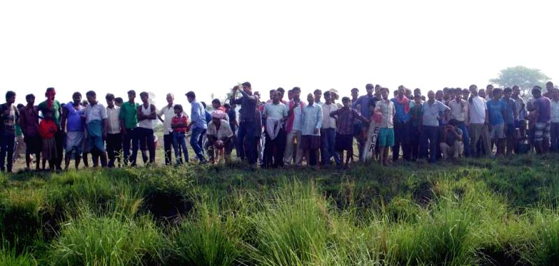 Locals gather at the site where nine out of twelve bogies of Delhi-Dibrugarh Rajdhani Express were derailed near Golden Ganj railway station in Bihar's Saran district on June 25, 2014. At least four .