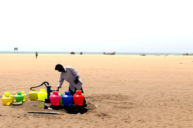Locals gather with their vessels to collect water at one of the hand-pumps installed near Marina Beach amid water crisis, in Chennai on July 9, 2019.