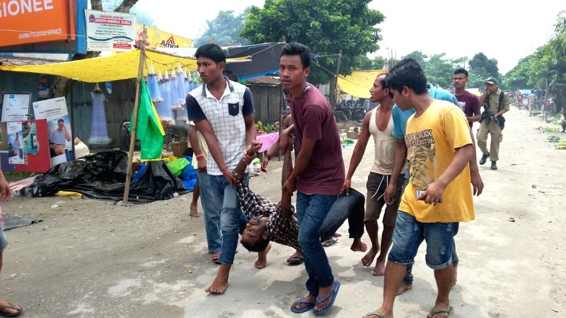 Locals take away body of a man killed in Kokrajhar terror attack on Aug 5, 2016. At least 12 civilians were killed on Friday when militants in military fatigues opened random fire at a ...