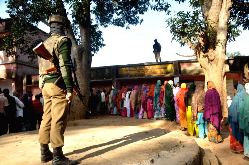 A security personnel stands guard at a polling booth during the first phase of Jharkhand assembly polls in Lohardaga district of the state on Nov 25, 2014.