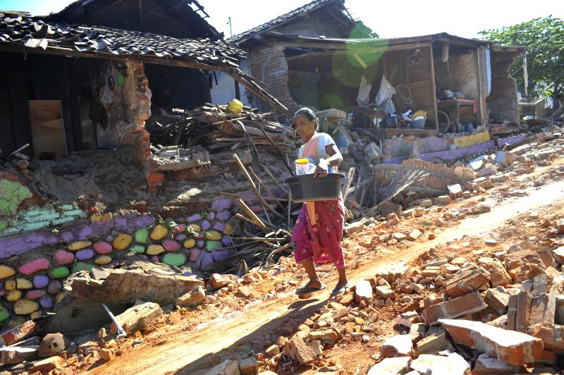 LOMBOK, Aug. 7, 2018 - A resident passes by a collapsed building in Lombok island, Indonesia, on Aug. 7, 2018. Death toll from Sunday's 7.0-magnitude quake in Indonesia reached 105 on Tuesday while a ...